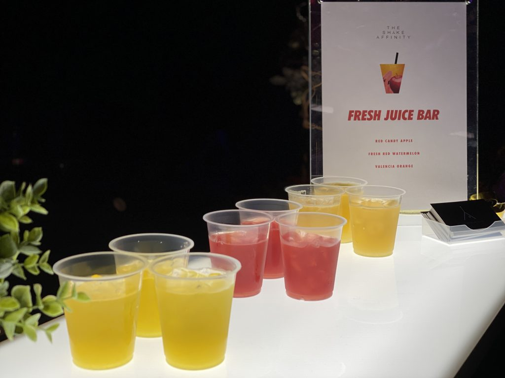 Apple, watermelon and orange fresh juice in cups on mobile cold press juice bar top