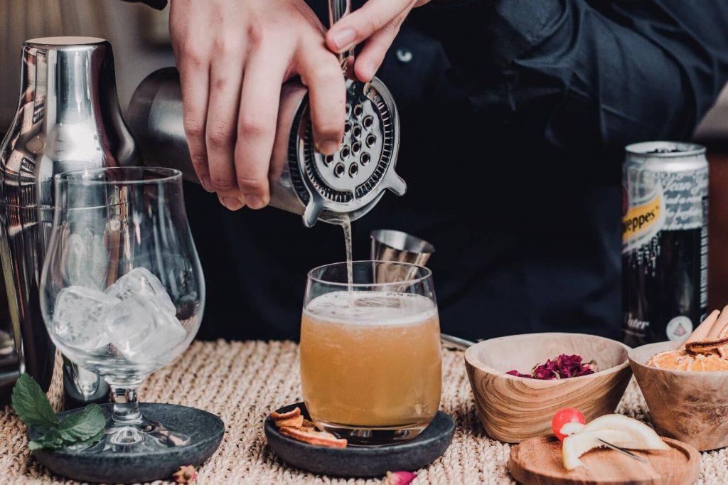 Bartender pouring shakened whiskey sour into glassware