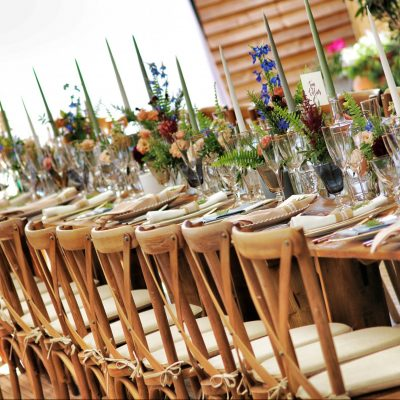 white padded wooden brown chairs with culinary places neatly with elegant flower center pieces